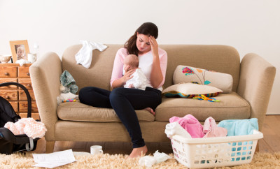 Mother with her baby on her knee. Her head is lowered as she sits on a sofa looking tired and stressed. The room looks untidy with clothes, nappies and other items scattered around the room.