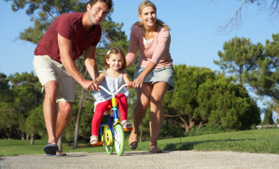 Parents Teaching Daughter To Ride Bike In Park Smiling And Cheering.