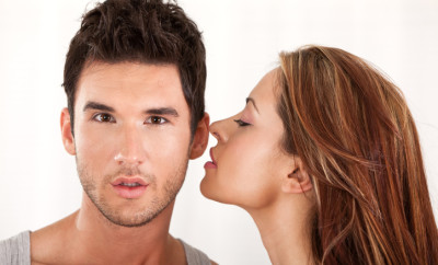 Passionate young couple, woman whisperinr to man's ear.