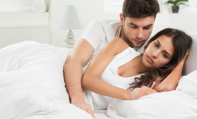 portrait of unhappy young heterosexual couple in bedroom