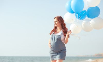 Portrait of smiling pregnant girl walking at sea shore holding balloons. Resting outdoors. Motherhood. Maternity.