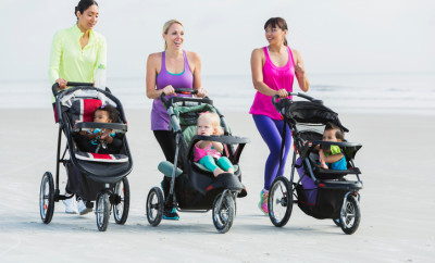 Three multi-ethnic mothers walking together on the beach, pushing their children in jogging strollers.  The child in the middle, a 22 month old toddler with blond hair, is the oldest.  The African American girl and Asian boy are 11 months old.