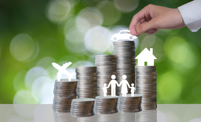 Coin stacks with travel  family  home  car on business man hand on green background , money and business idea concept