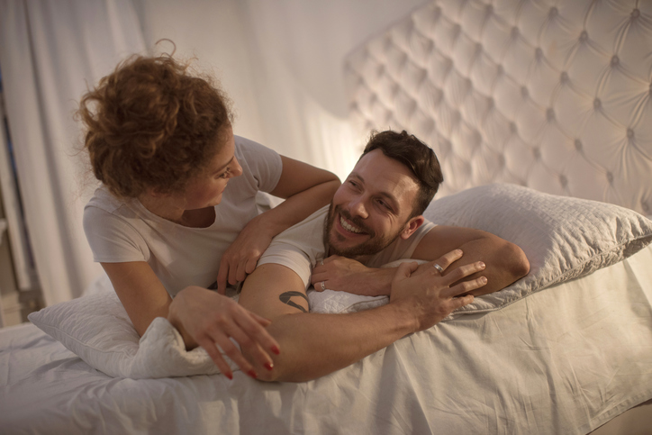 Young happy couple talking to each other in bed.