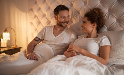Young smiling couple sitting in their bed and talking to each other.