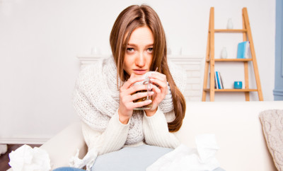 Sick woman with rheum holding a cup of tea