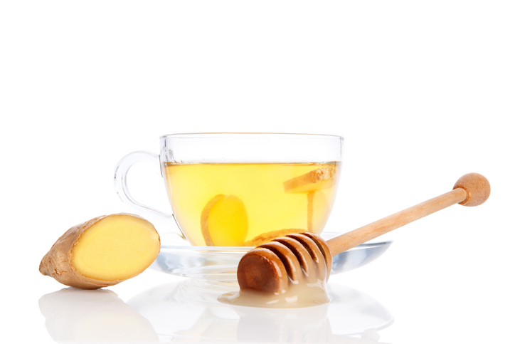 Cup of fresh ginger tea with ginger slices in transparent tea cup with saucer, honey and cut ginger root isolated on white background. Alternative natural medicine concept.