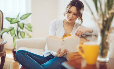 Content woman is reading a book on a white sofa at home. She is sitting comfortable and is wearing blue jeans and a grey sweater. The living room is cosy and elegant. Her hair and eyes are brown. Candid shot.