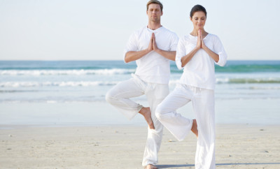 Full length shot of a two young people practicing yoga on the beach