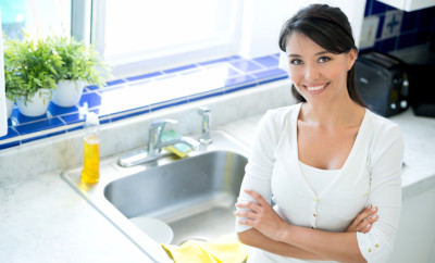 Woman in the kitchen washing dishes and standing next to the sink