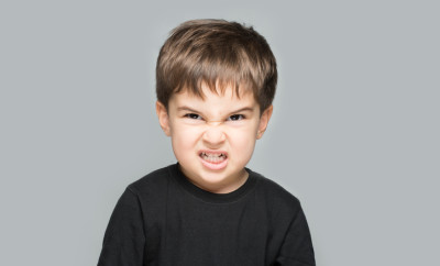 Mad outraged and furious kid posing in studio