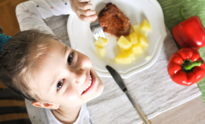 Young girl eating grilled tuna steak and boiled potatoes, Indoors shot of a little girl having a healthy meal decorated with red paprika and looking up at camera.
