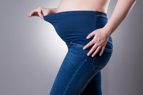 Pregnant woman in blue jeans for pregnant women