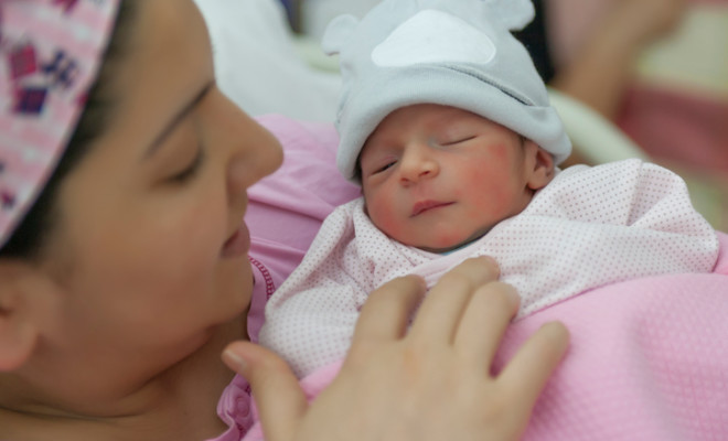 A newborn baby enters the world and mother holding newborn baby girl in the hospital.