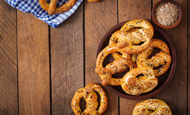 Oktoberfest salted soft pretzels in a bowl from Germany on wooden background. Top view