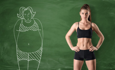 Sporty girl with a slim body standing at the right side and a picture of a fat woman drawn at the left side on a green chalkboard background. Getting rid of a pot belly. Losing weight. Before and after.