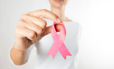 Woman holding pink ribbon, breast cancer awareness ribbon.
