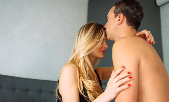 Portrait of two adult people - married couple in bedroom, in underwear. Blonde woman in 25-30 years old, husband holding her, hugging and kissing. Image taken with Nikon D800 and 24-70mm lens, developed from RAW. Slovakian and Italian ethnicities on the image.