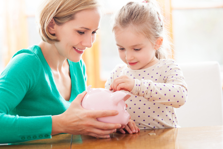 Smiling mother with daughter putting coins in a piggy bank