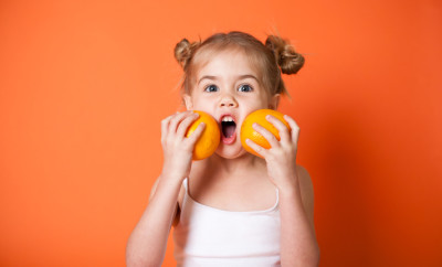 Color image of a cute little girl holding oranges while on an orange background.