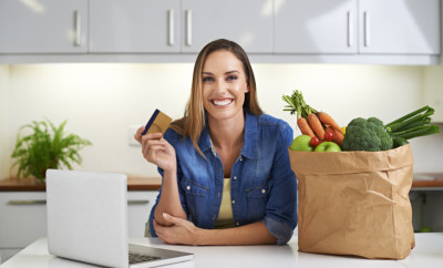 Cropped shot of a young woman doing some online shopping with her groceries beside her