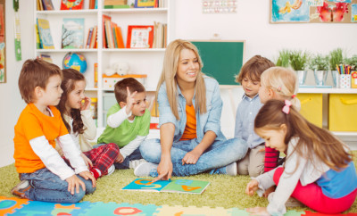 Teacher with a group of preschool children in a nursery. The children are sitting on the floor and listening  teacher. Learning letters. In the background we can see a shelf with some, toys, black board and books.