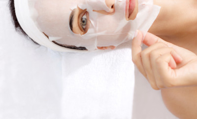 Caucasian female is taking off facial mask.