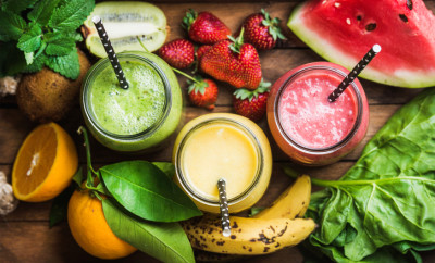 Freshly blended fruit smoothies of various colors and tastes in glass jars in rustic wooden tray. Yellow, red, green. Top view, selective focus