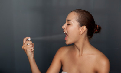 Woman spraying breath spray in her mouth