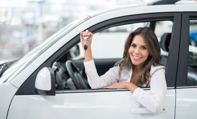 Woman buying a car and looking very happy