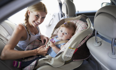 Mother (30s) putting baby girl (7 month) in car seat, buckling straps.