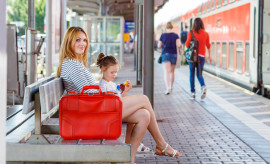 Cute little girl and mother on a railway station.