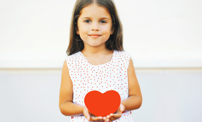 Portrait of cute little girl with red paper heart over white