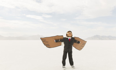 A young business boy dressed in business suit wearing cardboard wings and aviator goggles is ready to fly his business into the sky. He is standing on the Bonneville Salt Flats in Utah, USA.