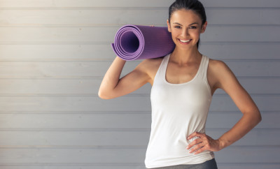 Beautiful young woman in sports wear is holding a yoga mat, looking at camera and smiling, standing on a gray background