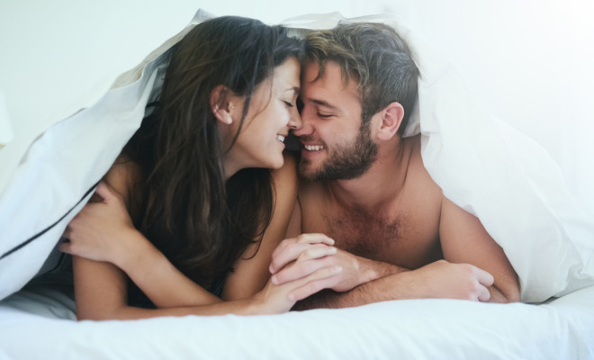 Shot of a young couple having an intimate moment under the covers