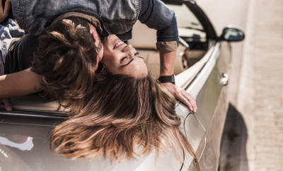 Close up of a young loving couple having a desire toward each other while lying on cabriolet.