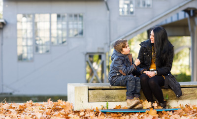 Mother and son sitting on bench and talking in front of abandoned railroad station