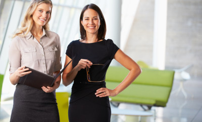 Businesswomen Having Informal Meeting In Modern Office Smiling To Camera