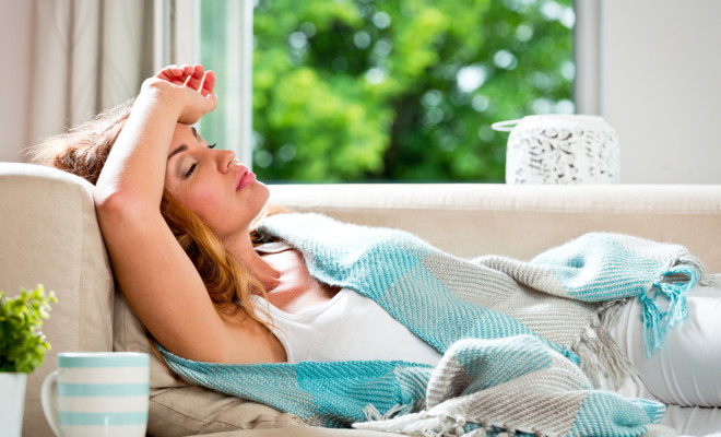 Woman have a headache, lying covered with blanket on sofa.
