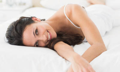 Happy brunette lying on bed at home in bedroom