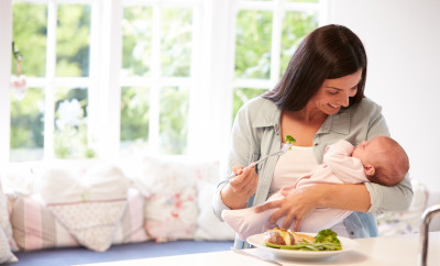 Mother With Baby Eating Healthy Meal In Kitchen