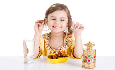 Young Muslim girl eating dates for brakfast in Ramadan - sitting on a table with water , dates , Quran, and Ramadan lantern.