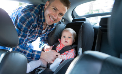 Shot of a father putting his daughter in a car seat. They are both looking at the camera, and smiling.