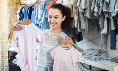 Woman buying baby sleep suit in kids in apparel shop