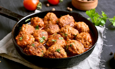 Meatballs with tomato sauce in frying pan, close up view