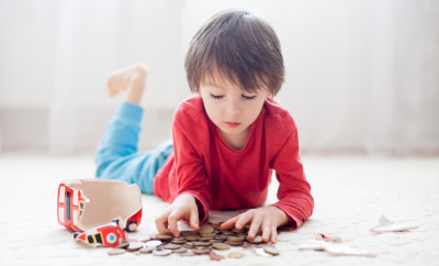 Little boy, breaking his piggy bank, emptying all saved money to buy gift for mother's day