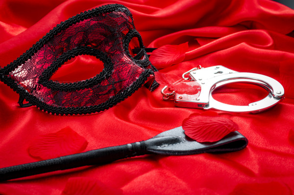 BDSM concept: crop, handcuffs and eyemask on red satin