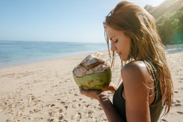Female tourist on beach vacation with coconut