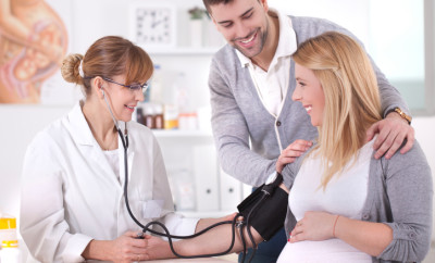 Doctor measuring blood pressure pregnant woman